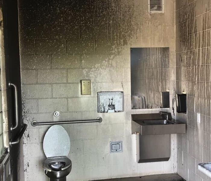 Public restroom with silver toilet covered in black soot.
