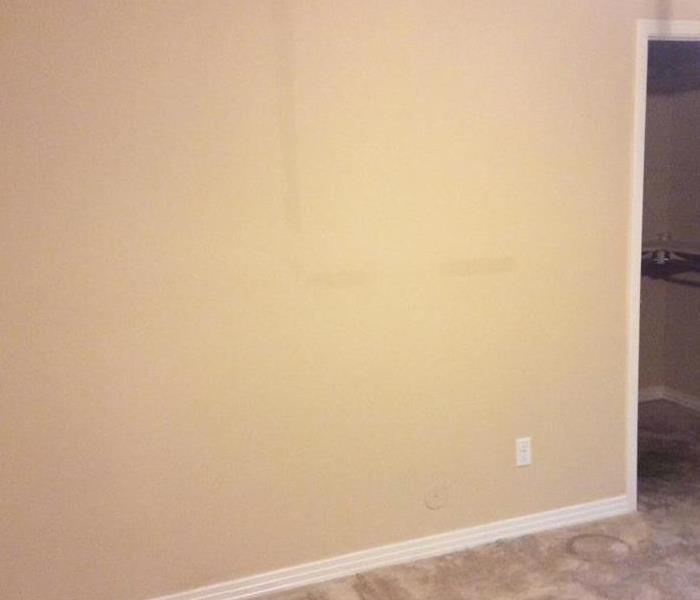 Yellow bedroom with dark water stains on the wall.