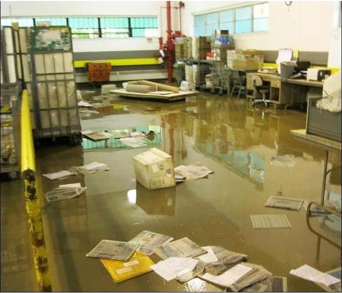 Inside of a building flooded, documents are on the floor and some containers in the water