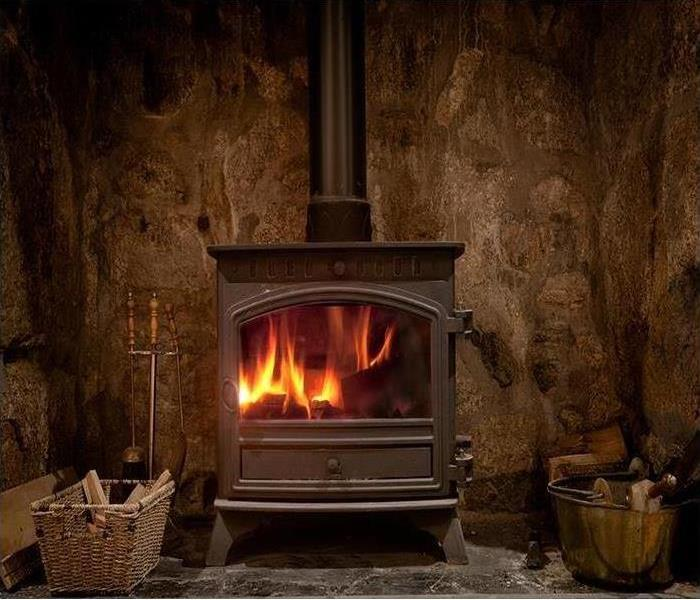 Roaring fire inside a wood burning stove in a rustic room