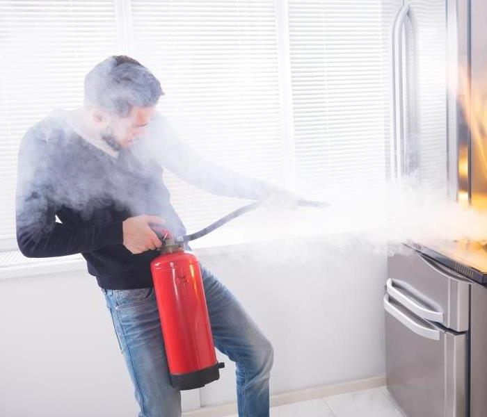 Man using fire extinguisher to put out a fire.